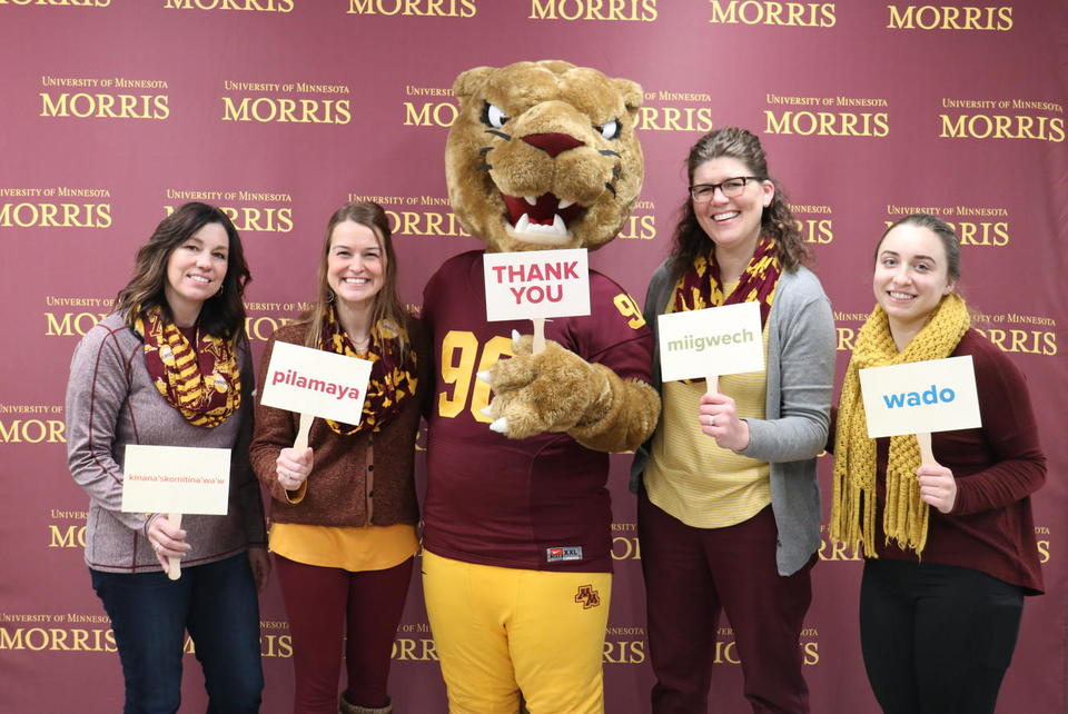 "Alumni Relations staff standing with Pounce the Cougar mascot, in front of a maroon backdrop with the UMN Morris wordmark, holding signs that read, ""Thank You"""