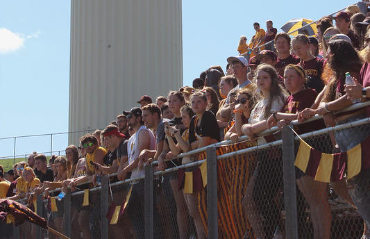 Students cheering on the football team during the homecoming game.